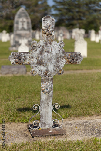 An unmarked grave with a metal cross.