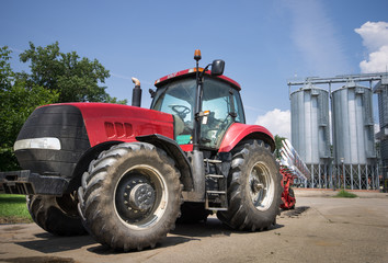 tractor in front of silos