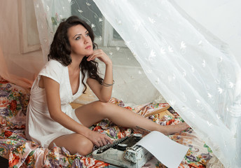 Gorgeous young brunette writer sitting on the bed and typing on
