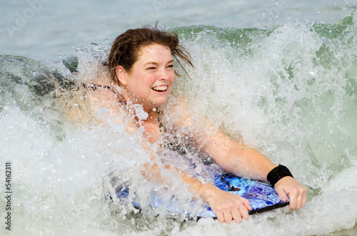 Woman surfing on bodyboard at beach