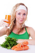 Sporty woman holding carrot juice and greens