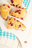 Scones with orange zest and berries on a cutting board