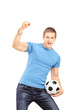 Euphoric fan holding a soccer ball and cheering