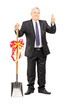 Mature businessman holding a shovel with ribbon on it and giving