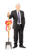 Full length portrait of an investor holding a shovel with ribbon