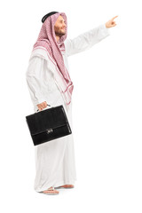 Full length portrait of a male arab person holding a suitcase an