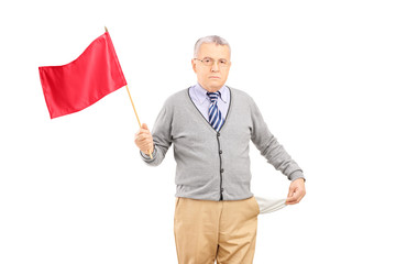 Sad senior man waving a red flag and showing his empty pocket