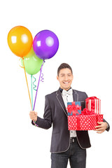 Smiling handsome guy holding presents and bunch of balloons