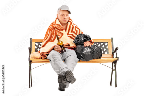 Drunk homeless mature man sitting on a bench and holding a bottl