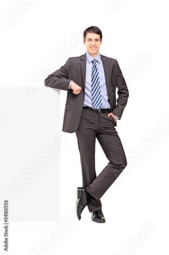 Full length portrait of a young businessman posing on a panel
