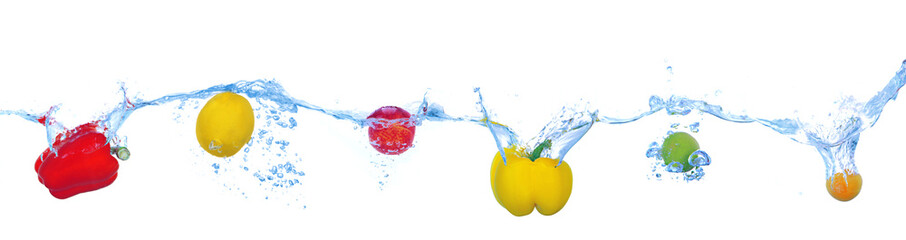 Tropical fruits and vegetables falling into water with splash