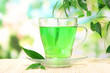 Transparent cup of green tea on bamboo mat, on nature