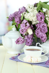 Composition with beautiful lilac flowers, tea service