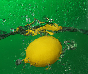 Juicy lemon under water, on green background