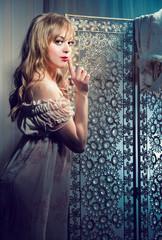 Beautiful blond woman making a hush gesture