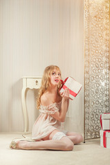 Sexy blond woman with a gift boxes posing indoors