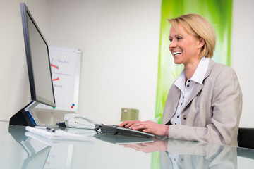 lächelnde sekretärin am computer