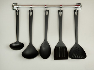 Black kitchen utensils on silver hooks, on grey background