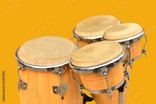 Leinwanddruck Bild Conga drum set on yellow background.