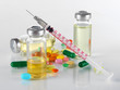 Medical bottles syringe and tablets on light gray background