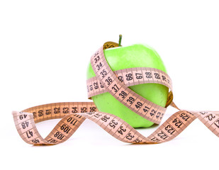 Measuring tape wrapped around a green apple.