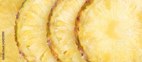 Row sliced pineapple. Close up. Whole background.