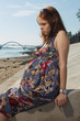 The young pregnant woman sits on a beach