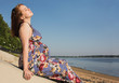 The pregnant woman sits on coast
