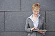 Frau benutzt Tablet Computer unterwegs