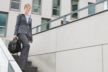 Junge Geschäftsfrau geht eine Treppe runter