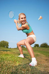 Fitness, young woman playing badminton in a city park