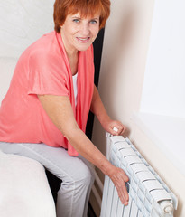 Woman controls the temperature of the radiator