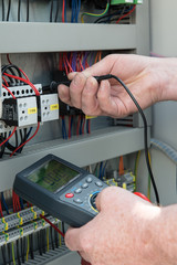 Elektriker prüft Spannung am Schaltschrank