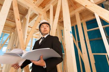 木造住宅の工事現場を確認する現場監督