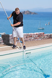 Man Cleaning Swimming Pool Above The Sea