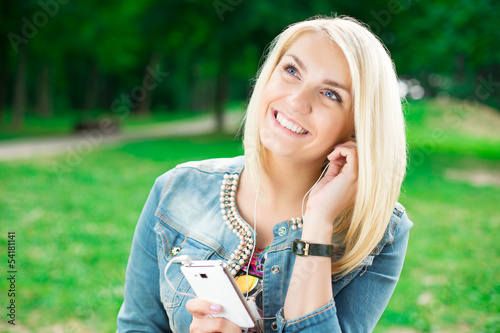 Young blond girl listening player