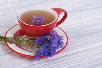 Tea with petals of wild cornflowers in a red cup on the table