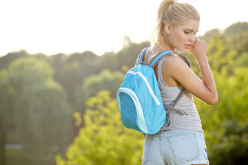 young blond woman hiking with scenery in thegreen landscape back