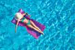 Junge Frau auf der Luftmatratze im Pool