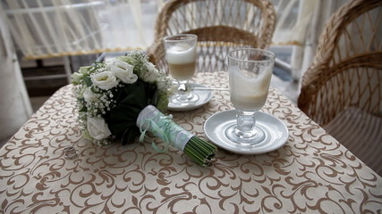 Two cups with cappuchino with wedding bouquet on the table