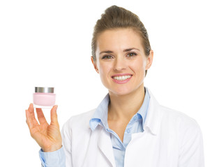 Smiling cosmetologist woman showing cream bottle