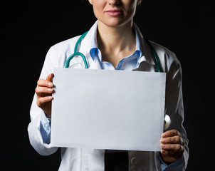 Closeup on doctor woman showing blank paper sheet isolated