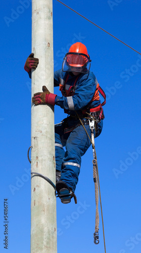 Electrician climbs the pole transmission line