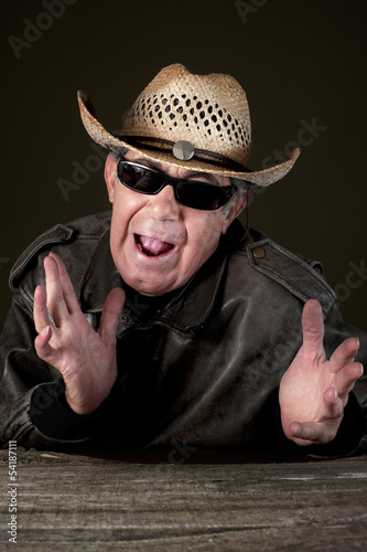 Confused man with hat and sunglasses in black background