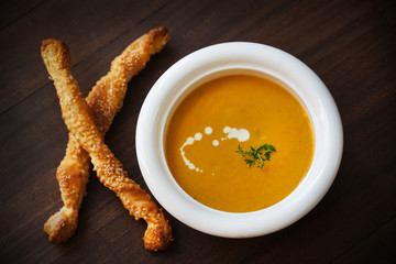 Creamy soup of carrots, potatoes, thyme and sesame breadsticks