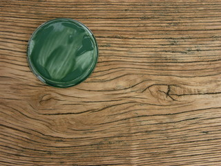 Unbehandeltes Hold mit Maserung und grünem Deckel