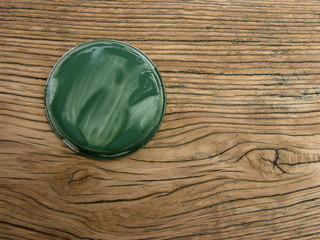 Grüner Farbdeckel und unbehandeltes Holz einer Parkbank