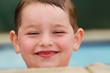 Portrait of smiling, happy child at side of pool