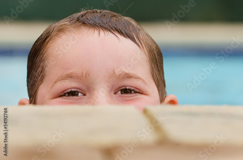 Portrait of child peeking over edge of pool while swimming