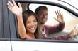 Drivers driving in car waving happy at camera